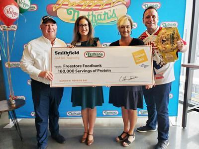 (From left to right) Vice President of National Accounts at Smithfield Foods Tim Totin, Corporate Affairs Manager for Kroger Cincinnati-Dayton Division Erin Rolfes, Chief Development Officer & VP of External Affairs at Freestore Foodbank Trisha Rayner, and Competitive Eater Joey Chestnut gather in Cincinnati on National Hot Dog Day for a donation of 160,000 servings of protein to Freestore Foodbank.
