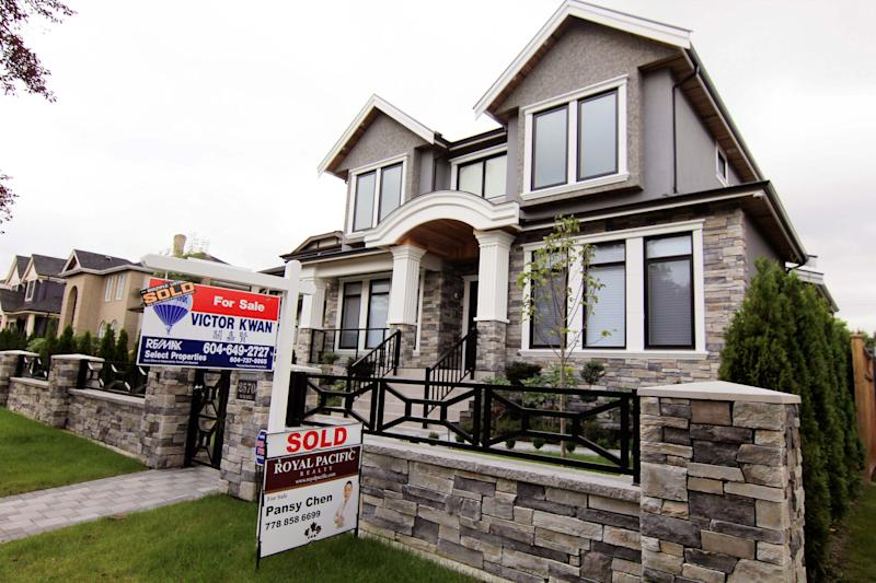 Realtors' signs are hung outside a newly sold property in a Vancouver neighborhood in this file photo