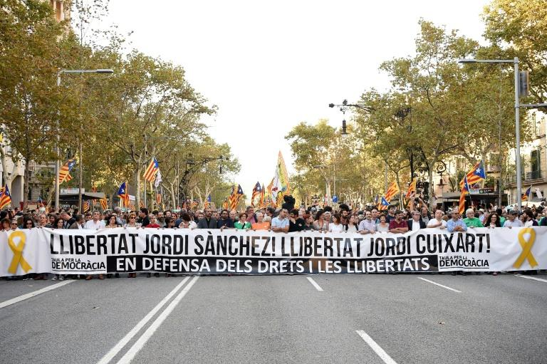 "​People hold a giant banner reading ""Freedom for Jordi Sanchez! Freedom for Jordi Cuixart!"" during a rally in Barcelona, to support two leaders of Catalan separatist groups who have been detained pending an investigation into sedition charges"