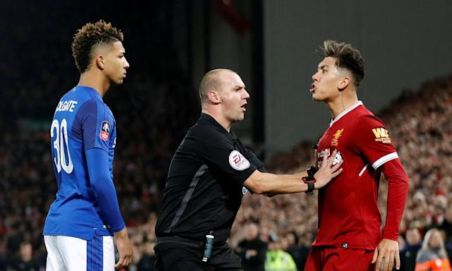 The referee Bobby Madley separates Everton's Mason Holgate and Liverpool's Roberto Firmino after the two players clashed on 5 January.