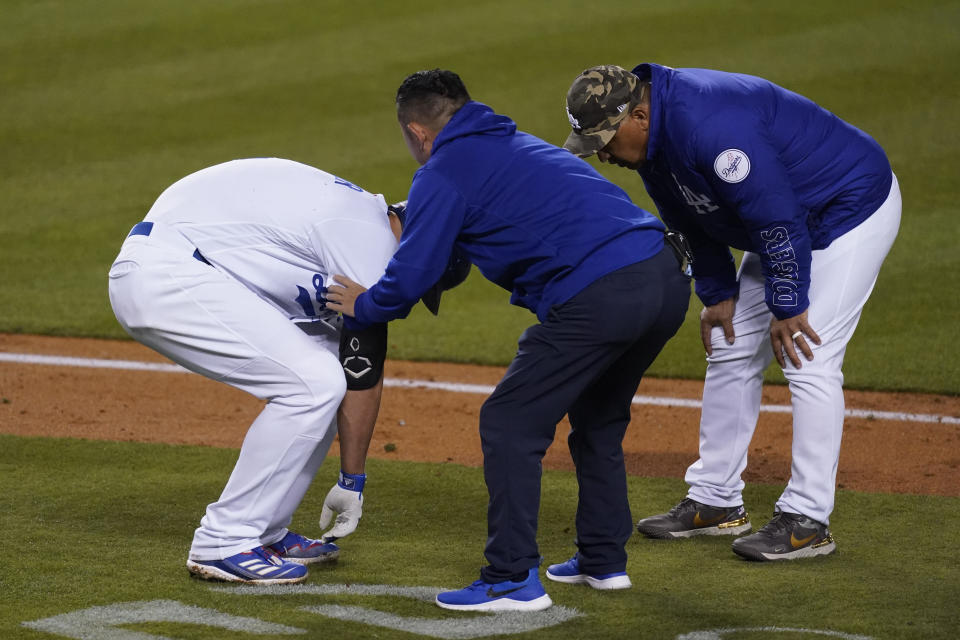 Los Angeles Dodgers' Corey Seager, left, reacts after being hit by a pitch from Miami Marlins relief pitcher Ross Detwiler (54) during the fifth inning a baseball game Saturday, May 15, 2021, in Los Angeles. (AP Photo/Ashley Landis)