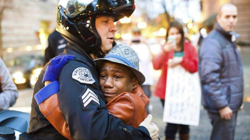 Devonte Hart gained fame when this picture of him hugging officer Johnny Nguyen at a Portland rally went viral. He is one of three children still missing after the vehicle went over the cliff. Source: AP