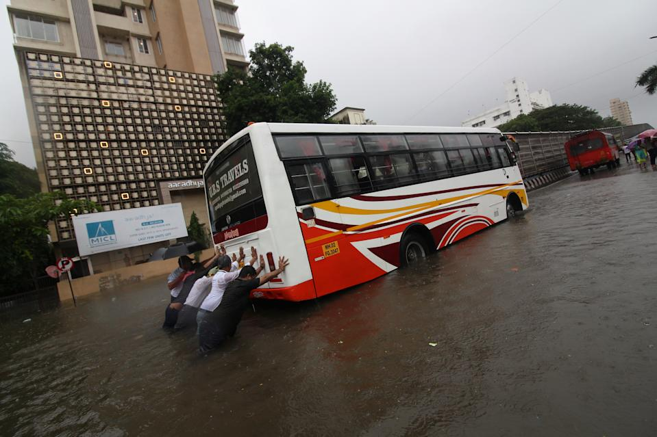 People push a bus through a flooded road during heavy rains in Mumbai, India on August 04, 2020. (Photo by Himanshu Bhatt/NurPhoto via Getty Images)