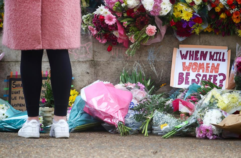 A person stands near flowers at a memorial site in Clapham Common Bandstand, following the kidnap and murder of Sarah Everard, in London, Britain March 13, 2021. REUTERS/Hannah McKay     TPX IMAGES OF THE DAY