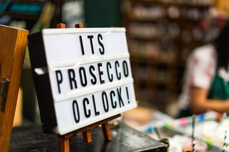 Close up color image of a fun handmade wooden sign with the words 'It's Prosecco o'clock'. The image was taken at a food and drink market in London, UK. In the background the market, and a female figure working on the stall, is defocused, leaving room for copy space.