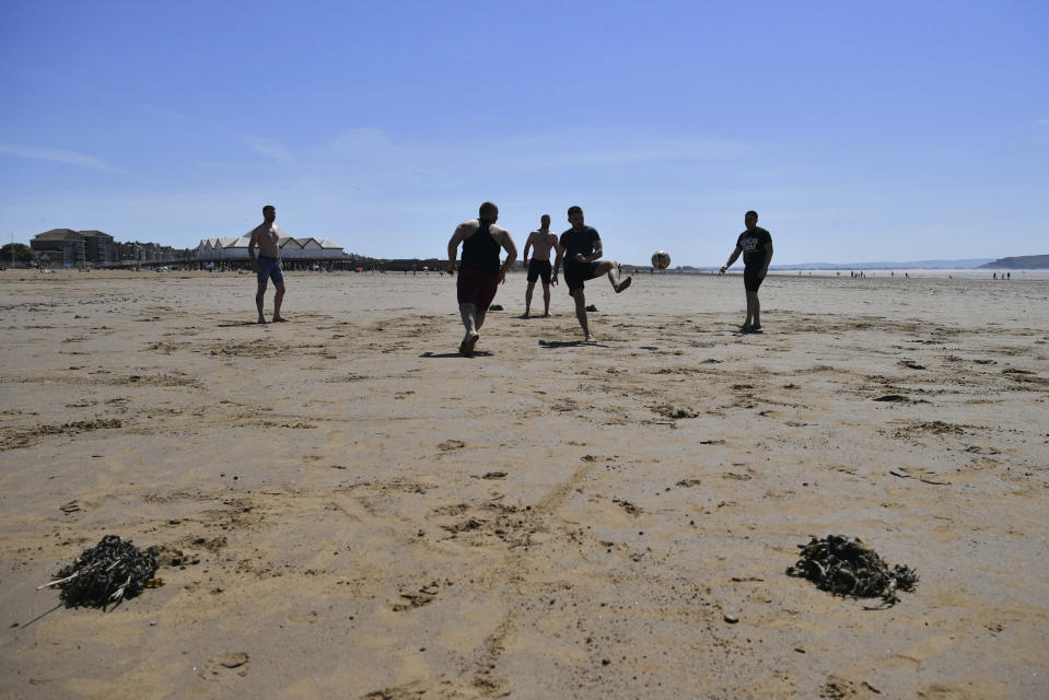 Men play football as they enjoy the hot weather on the beach, in Weston-super-Mare, England, Wednesday May 20, 2020. Lockdown restrictions due to the coronavirus outbreak have been relaxed allowing unlimited outdoor exercise and activities such as sunbathing. The Met Office has predicted the hottest day of the year so far with temperatures set to hit 28C (82.4F). (Ben Birchall/PA via AP)