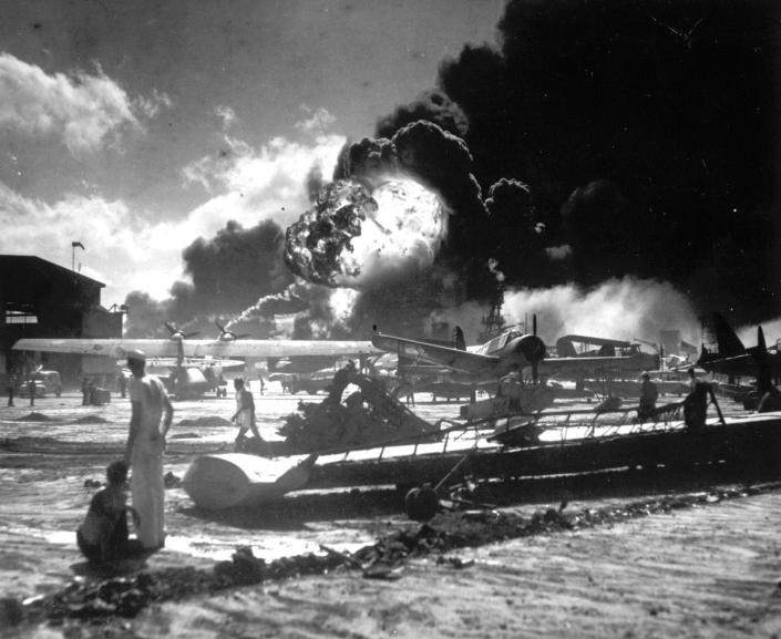 <p>In this image provided by the U.S. Navy, sailors stand among wrecked airplanes at Ford Island Naval Air Station as they watch the explosion of the USS Shaw in the background, during the Japanese surprise attack on Pearl Harbor, Hawaii, on December 7, 1941. (AP Photo/U.S. Navy) </p>