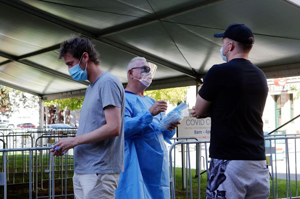 Two men with face masks stand near a medical worker at a Covid-19 testing centre in Perth.