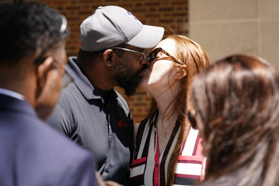 Former NFL player Clarence Vaughn III, center left, and his wife Brooke Vaughn kiss before delivering tens of thousands of petitions demanding equal treatment for everyone involved in the settlement of concussion claims against the NFL, to the federal courthouse in Philadelphia, Friday, May 14, 2021. (AP Photo/Matt Rourke)