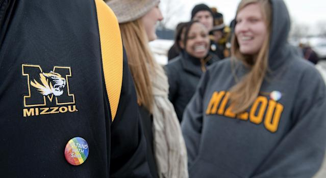 Drew Carlton wears a #Stand With Sam button as he joins several hundred supporters of Michael Sam stand along Stadium Boulevard across the street from Memorial Stadium Saturday, Feb. 15, 2014, in Columbia, Mo. (AP Photo/L.G. Patterson)