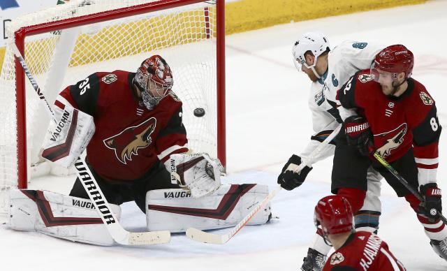 Arizona Coyotes goaltender Darcy Kuemper (35) gives up a goal to San Jose Sharks' Logan Couture, not seen, as Sharks center Joe Pavelski (8) and Coyotes defensemen Jordan Oesterle (82) and Niklas Hjalmarsson (4) watch during the third period of an NHL hockey game Wednesday, Jan. 16, 2019, in Glendale, Ariz. The Coyotes defeated the Sharks 6-3. (AP Photo/Ross D. Franklin)