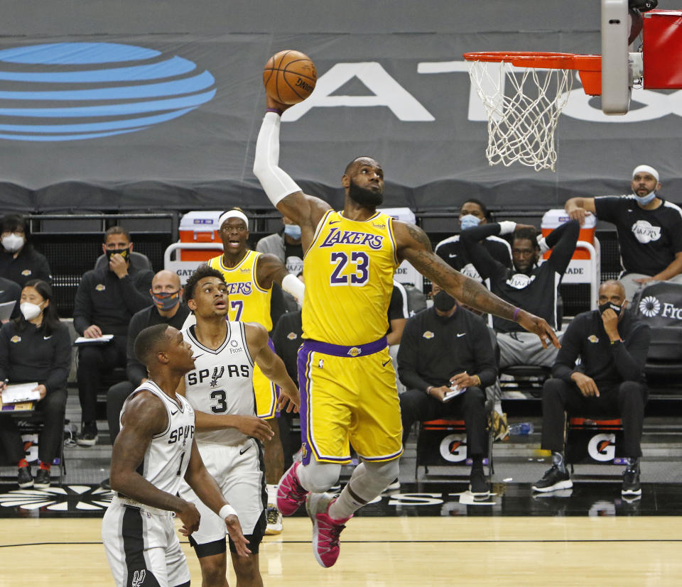 SAN ANTONIO, TX - DECEMBER 30  LeBron James #23 of the Los Angeles Lakers dunks past spurs defenders during first half action at AT&T Center on December   30, 2020 in San Antonio, Texas.  NOTE TO USER: User expressly acknowledges and agrees that , by downloading and or using this photograph, User is consenting to the terms and conditions of the Getty Images License Agreement. (Photo by Ronald Cortes/Getty Images)