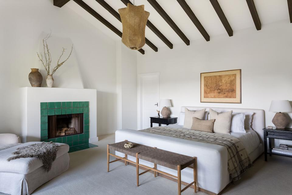 "<div class=""caption""> ""It feels almost like a resort room,"" says Page of the couple's grand main bedroom. The green tile around the fireplace, which is original to the home, was a contentious item at first—Elliott wasn't a fan while Page and Boesch loved it—but she eventually came around to appreciating the pop of color. The bed is from <a href=""https://www.onekingslane.com/"" rel=""nofollow noopener"" target=""_blank"" data-ylk=""slk:One Kings Lane"" class=""link rapid-noclick-resp"">One Kings Lane</a>, with linens from <a href=""https://www.parachutehome.com/"" rel=""nofollow noopener"" target=""_blank"" data-ylk=""slk:Parachute"" class=""link rapid-noclick-resp"">Parachute</a>, and Boesch designed the pillows herself with custom vintage fabric. The unique pendant lamp is from <a href=""https://rghomeandgarden.com/"" rel=""nofollow noopener"" target=""_blank"" data-ylk=""slk:Rolling Greens"" class=""link rapid-noclick-resp"">Rolling Greens</a>. </div>"