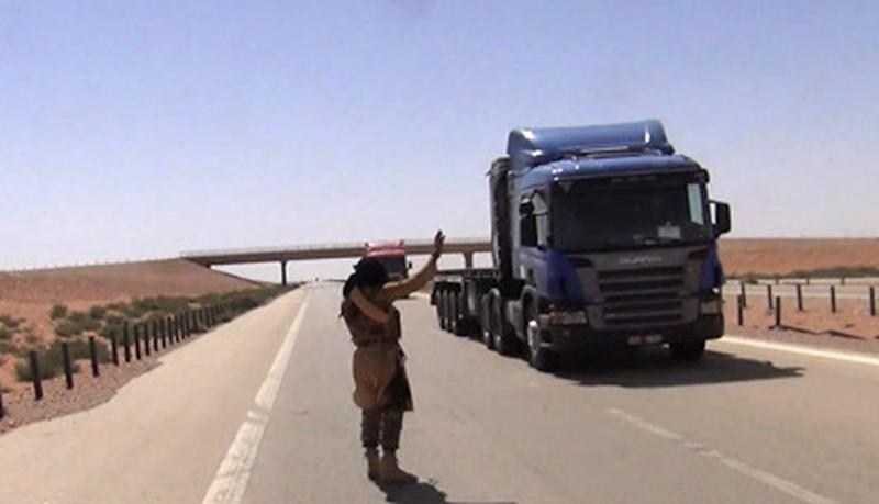 This undated image made from video posted on a militant website in Aug. 2013, with is consistent with other AP reporting, purports to show a jihadi militant flagging down a truck on a major highway in western Iraq. The video shows militants stopping three Syrian truck drivers, interrogating them, then gunning them down, believing them to be members of the Alawite sect. The incident, as well as another posted video of a mob stringing up a suspected terrorist's shirtless body by the feet and set it ablaze on a street on the outskirts of the Iraqi capital, both confirmed by police, illustrate in stark terms the increasing brutality of the unrest gripping Iraq, fueling complaints that security forces are unable to contain it. (AP Photo via militant website)