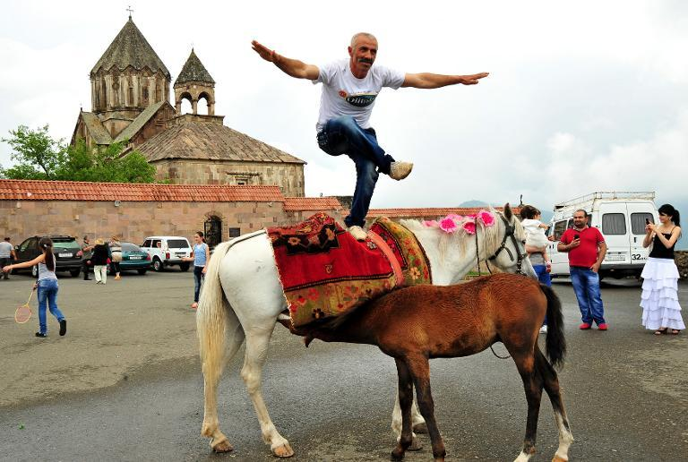 A man dances on a horse in front of 13th century's St.John Cathedral in the Armenian-controlled Azerbaijani region of Nagorny Karabakh on June 27, 2013