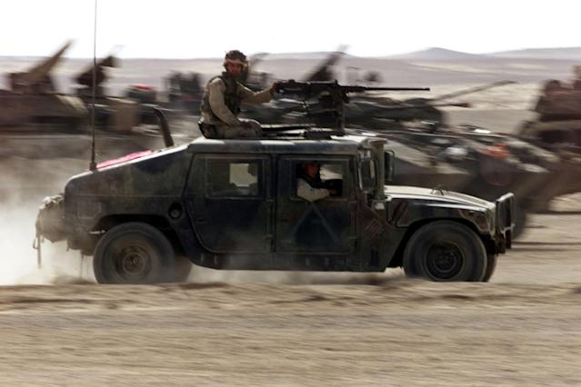 <p>A US Marine Humvee kicks up dust as it crosses a group of Marine LAVs (Light Armoured Vehicles) as it leaves on patrol from the Marine base in southern Afghanistan Dec. 2, 2001. (Photo: Jim Hollander/Reuters) </p>