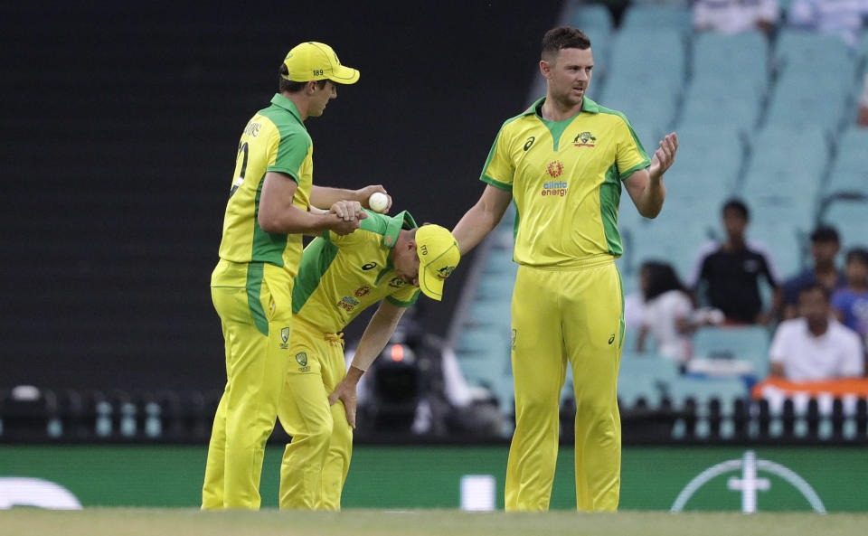 Australia's David Warner, centre, is assisted by teammates Pat Cummins, left, and Josh Hazlewood after injuring himself while fielding during the one day international cricket match between India and Australia at the Sydney Cricket Ground in Sydney, Australia, Sunday, Nov. 29, 2020. (AP Photo/Rick Rycroft)