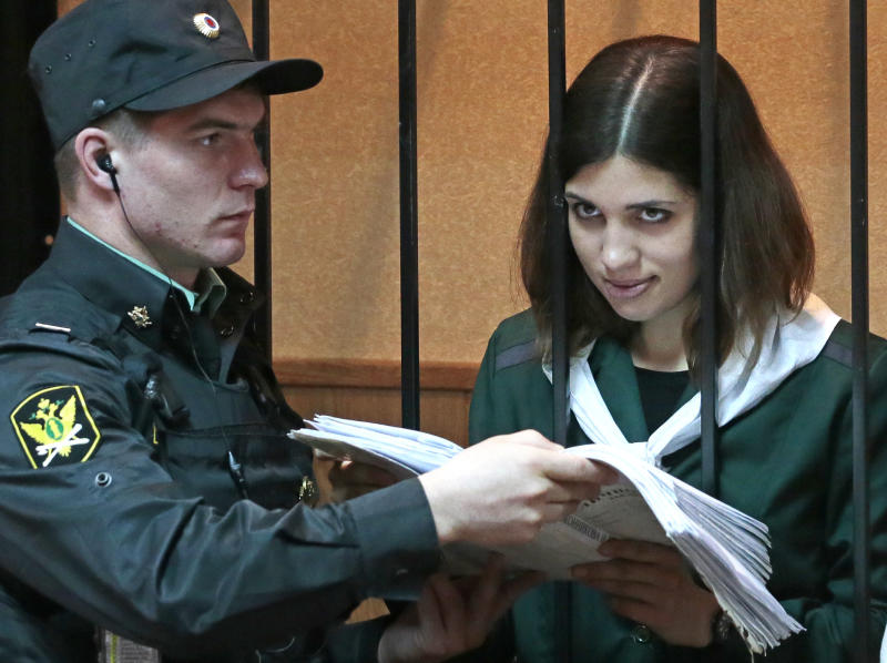 Nadezhda Tolokonnikova, a member of the feminist punk band, Pussy Riot, right, reads papers at a district court in Zubova Polyana 440 km southeast of Moscow in Russia's province of Mordovia, Friday, April 26, 2013. A Russian court is to consider whether one of the jailed Pussy Riot members is eligible for early release. Nadezhda Tolokonnikova, in custody since her arrest in March 2012, is serving a two-year sentence for the band's irreverent protest against President Vladimir Putin in Moscow's main cathedral. Tolokonnikova's lawyer Irina Khrunova is at right.(AP Photo/Mikhail Metzel)