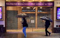 People walk past a closed Broadway theater in New York in October 2020, after the trade organization representing producers and theater owners announced that performances in New York City will be suspended through May 30, 2021 due to coronavirus
