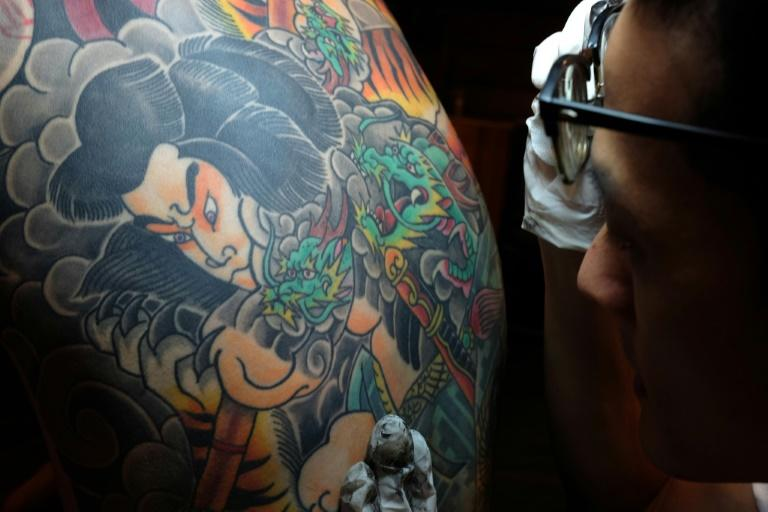 Bobo Chen inspects the inked back of his client Micky Peng in Taipei