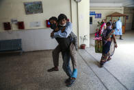 A man carries another on his back bringing him for a medical check up at a government hospital in Jammu, India, Monday, June 21, 2021. (AP Photo/Channi Anand)