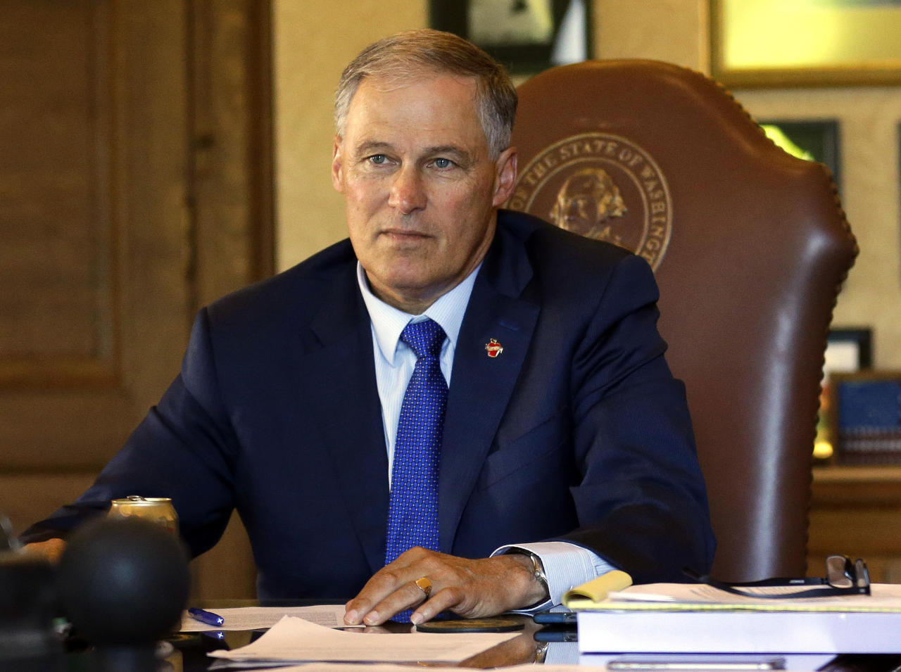 """FILE--In this June 30, 2017, file photo, Washington Gov. Jay Inslee, left, listens as he meets with staff members in his office as they review the state operating budget passed by the Legislature earlier in the day at the Capitol in Olympia, Wash. Inslee, along with Alaska Gov. Bill Walker, is asking the Trump administration to back off when it comes to marijuana and Inslee said Attorney General Jeff Sessions made claims about the situation in Washington that are """"outdated, incorrect, or based on incomplete information.""""(AP Photo/Ted S. Warren, file)"""