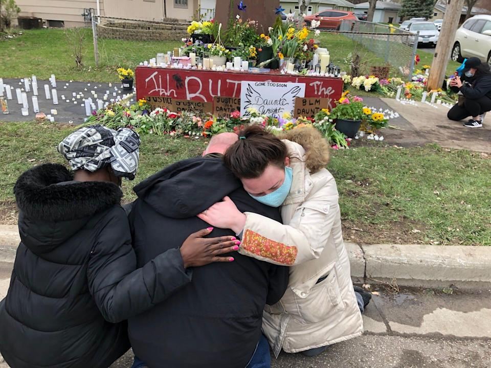Jamesetta Collins (left), Samuel Howell and Katie Russell pay their respects Tuesday near a Daunte Wright memorial in Brooklyn Center, Minnesota. The memorial site, a giant, rust-brown sculpture of a clenched fist, is surrounded by flower bouquets, messages and candles. Wright, a 20-year-old Black man, was fatally shot by a police officer during a traffic stop on Sunday.