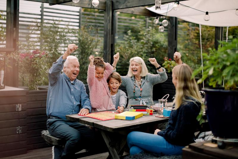 Cheerful family playing board game while sitting at table in backyard