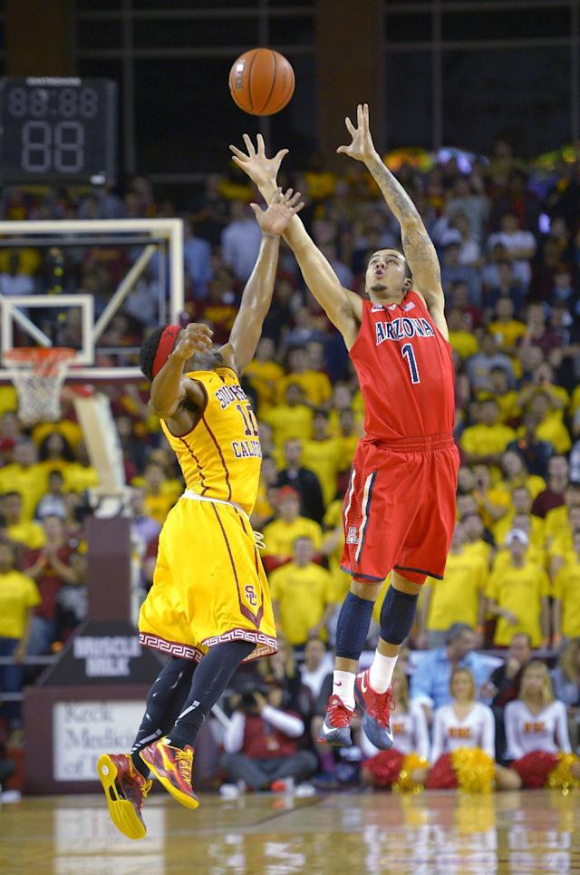 Arizona guard Gabe York, right, catches a pass as Southern California guard Pe'Shon Howard defends during the first half of an NCAA college basketball game, Sunday, Jan. 12, 2014, in Los Angeles. (AP Photo/Mark J. Terrill)