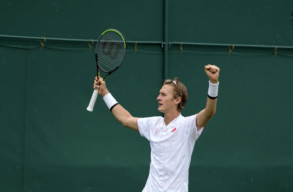 Sebastian Korda of the US celebrates defeating Australia's Alex De Minaur after the men's singles first round match on day two of the Wimbledon Tennis Championships in London, Tuesday June 29, 2021. (AP Photo/Alastair Grant)
