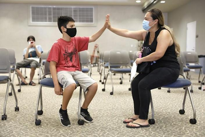 """TORRANCE-CA-JULY 7, 2021: Zuly Gomez, 42, right, congratulates her son Dean, 13, left, after receiving his first dose of the Pfizer vaccine at El Camino College in Torrance on Wednesday, July 7, 2021 as the college hosts a one-day COVID-19 vaccination clinic on campus, run by Providence, open to the public for individuals aged 12 and up. In anticipation of her son's in person school year coming up, Gomez said, """"It's better safe than sorry. I just feel strongly about the science and I just think it's better this way."""" (Christina House / Los Angeles Times)"""
