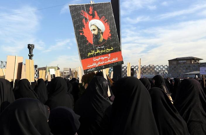 Iranian women gather during a demonstration against the execution of prominent Shiite Muslim cleric Nimr al-Nimr (portrait) by Saudi authorities, at Imam Hossein Square in the capital Tehran on January 4, 2016 (AFP Photo/Atta Kenare)