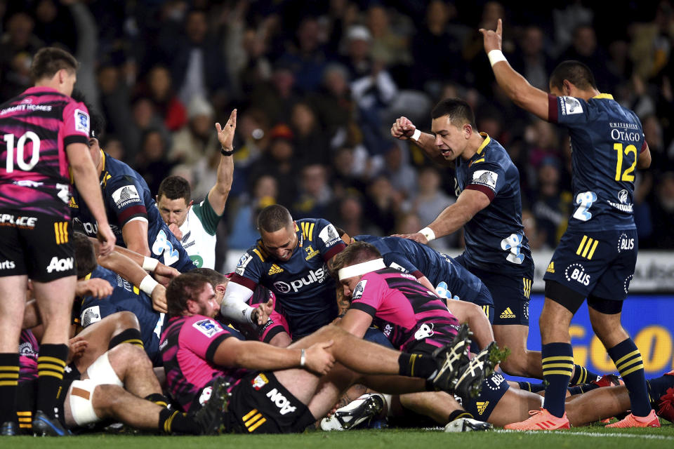 The Highlanders celebrate after scoring their first try during the Super Rugby Aotearoa rugby game between the Highlanders and Chiefs in Dunedin, New Zealand, Saturday, June 13, 2020. Super Rugby Aotearoa is the first major rugby union tournament to resume since the COVID-19 outbreak and one of the first major sports events in the world at which there will be no limitation on crowd size. (Joe Allison/Photosport via AP)