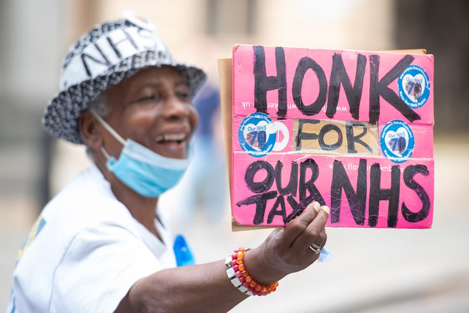 A woman holds a 'honk for our NHS' sign in Parliament Square, London, during a national protest by NHS workers over pay. (Photo by Dominic Lipinski/PA Images via Getty Images)