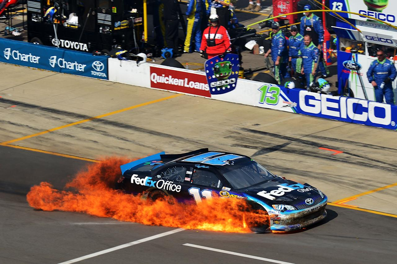 BROOKLYN, MI - JUNE 17:  Denny Hamlin drives the #11 FedEx Office Toyota on pit road as it bursts into flames after an incident during the NASCAR Sprint Cup Series Quicken Loans 400 at Michigan International Speedway on June 17, 2012 in Brooklyn, Michigan.  (Photo by Drew Hallowell/Getty Images for NASCAR)