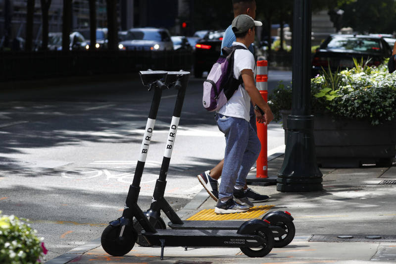 Pedestrians walk past a electric scooters Thursday, Aug. 8, 2019, in Atlanta. Atlanta is banning electric scooters during nighttime hours during a deadly summer for riders. The ban comes as cities across the nation struggle to regulate the companies renting the devices and keep riders safe. In Atlanta, three riders have died since May in Atlanta crashes that involved a public bus, an SUV and a car. Police in the Atlanta suburb of East Point say a fourth rider was killed there Tuesday in a collision involving his scooter and a truck. (AP Photo/John Bazemore)