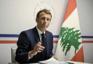 France's President Emmanuel Macron gestures as he attends an international video conference at the Fort de Bregancon, in Bormes-Les-Mimosas, southern France, Wednesday, Aug. 4, 2021. The virtual event, co-hosted by France and the United Nations, is meant to show support towards Lebanese people, French President Emmanuel Macron said. France will provide 100 millions euros ($118.6 million) in the coming months, Macron said in his opening remarks. (Christophe Simon/Pool Photo via AP)