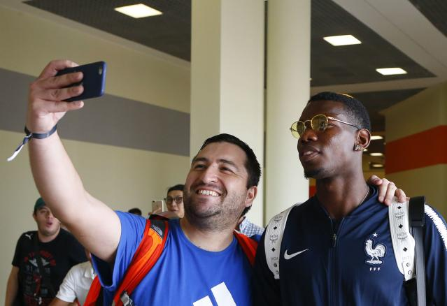 Soccer Football - World Cup - France Departure - Sheremetyevo International Airport, Moscow Region, Russia - July 16, 2018. Paul Pogba poses for a selfie picture with a football supporter before the departure. REUTERS/Sergei Karpukhin