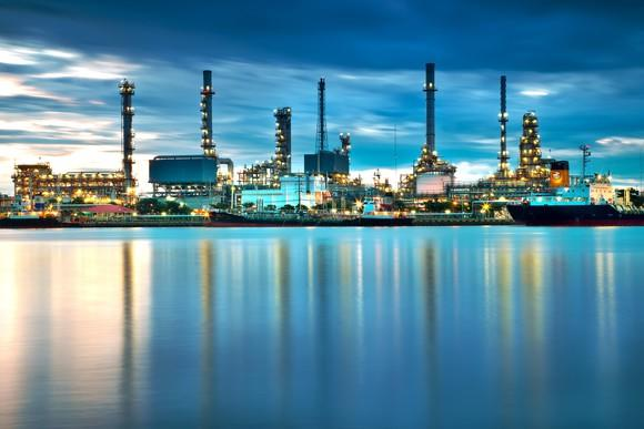 Oil refinery with multiple smokestacks at dusk near a waterfront.