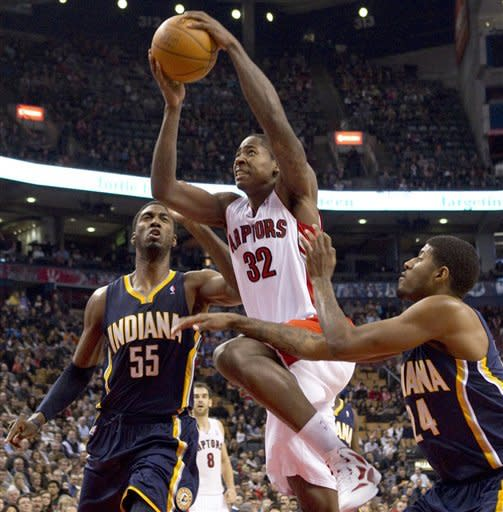 Toronto Raptors' Ed Davis (32) is fouled by Indiana Pacers Paul George (24) as Roy Hibbert looks on during first half NBA basketball action in Toronto, Friday, Jan. 13, 2012. (AP Photo/The Canadian Press, Chris Young)