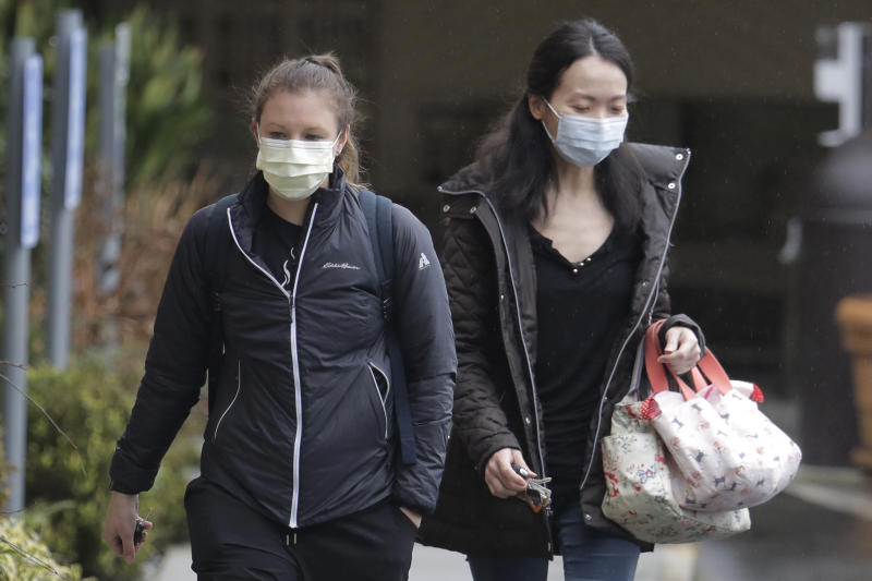 Two women wearing masks walk away from the Life Care Center in Kirkland, Wash., near Seattle, Monday, March 2, 2020. Health officials in Washington state said Sunday night that a second person had died from the coronavirus. (AP Photo/Ted S. Warren)