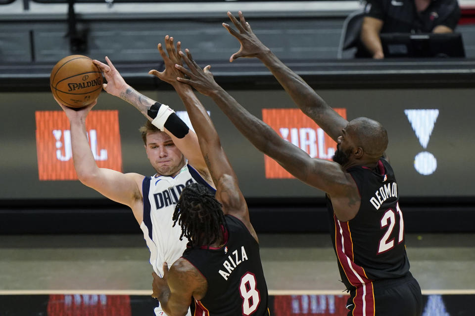 Dallas Mavericks guard Luka Doncic, left, passes past Miami Heat forward Trevor Ariza (8) and center Dewayne Dedmon (21) during the first half of an NBA basketball game, Tuesday, May 4, 2021, in Miami. (AP Photo/Wilfredo Lee)
