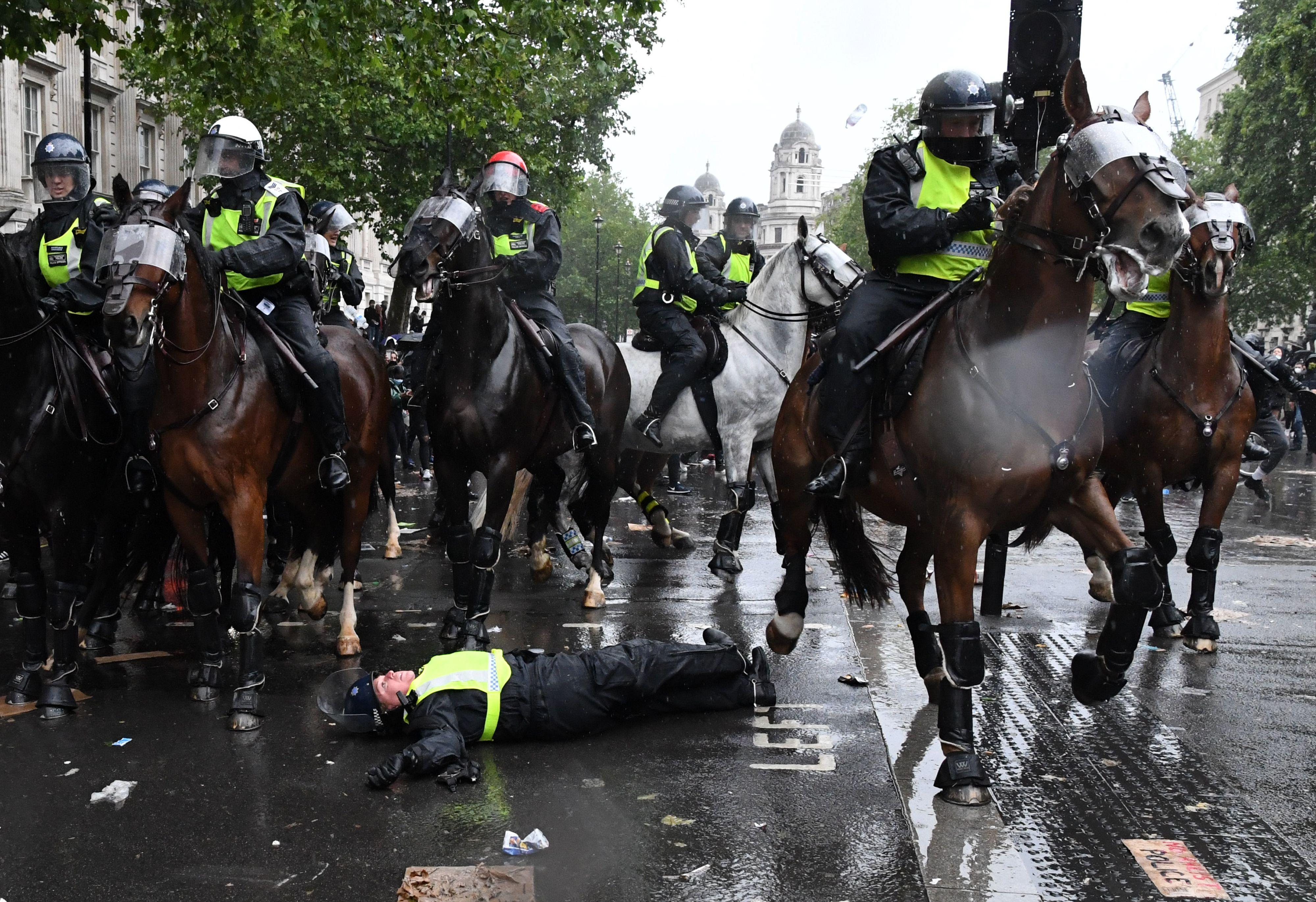 """TOPSHOT - A mounted police officer lays on the road after being unseated from their horse, during a demonstration on Whitehall, near the entrance to Downing Street in central London on June 6, 2020, to show solidarity with the Black Lives Matter movement in the wake of the killing of George Floyd, an unarmed black man who died after a police officer knelt on his neck in Minneapolis. - The United States braced Friday for massive weekend protests against racism and police brutality, as outrage soared over the latest law enforcement abuses against demonstrators that were caught on camera. With protests over last week's police killing of George Floyd, an unarmed black man, surging into a second weekend, President Donald Trump sparked fresh controversy by saying it was a """"great day"""" for Floyd. (Photo by DANIEL LEAL-OLIVAS / AFP) (Photo by DANIEL LEAL-OLIVAS/AFP via Getty Images)"""