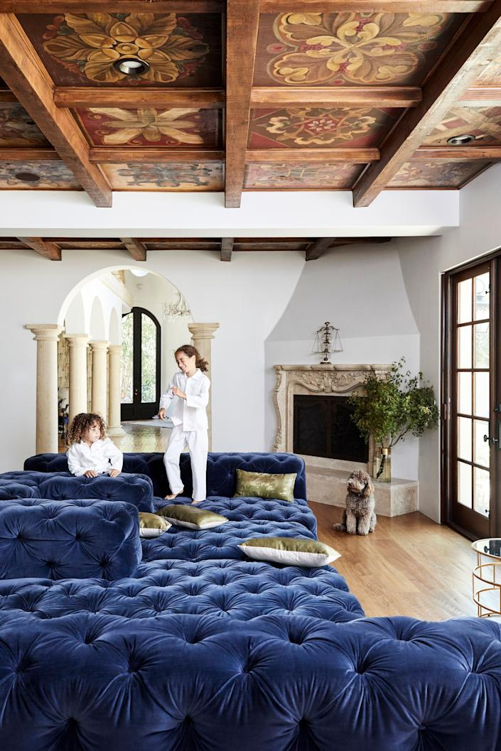 "<div class=""caption""> The family area off the kitchen is a favorite place for the children to play. Here, Isaiah (left) and Abraham hang out on the oversized Restoration Hardware couch. The ceiling panels were installed by the previous owners and were hand-painted by local artisans. </div>"