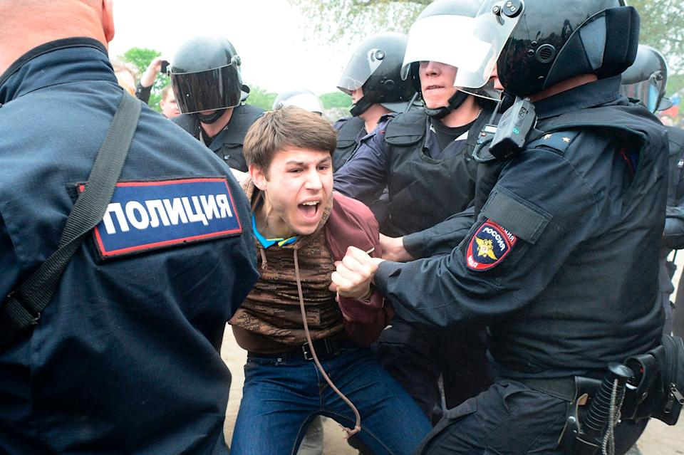 Russian police officers detain a participant of an unauthorized opposition rally in Saint Petersburg on June 12, 2017.