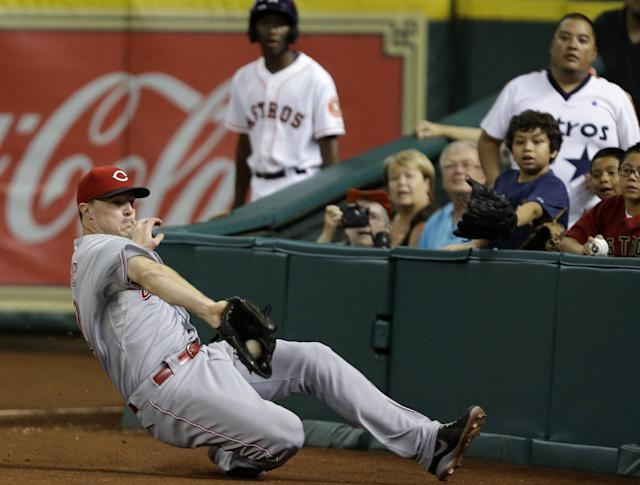 Cincinnati Reds right fielder Jay Bruce makes a sliding catch in foul territory for an out on Houston Astros' Jose Altuve in the ninth inning of a baseball game Wednesday, Sept. 18, 2013, in Houston. (AP Photo/Pat Sullivan)
