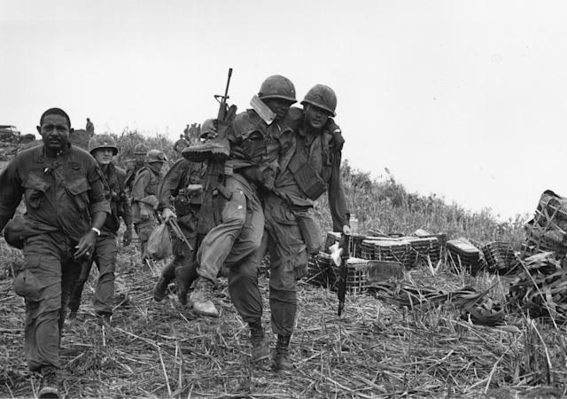 <p>11th April 1968: US soldiers, one wounded and being carried by a colleague, walking down Hill Timothy, during the conflict in Vietnam. (Photo: Terry Fincher/Daily Express/Hulton Archive/Getty Images) </p>