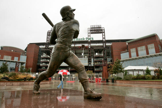 "FILE - In this Oct. 28, 2008, file photo, a statue of Philadelphia Phillies Hall of Fame third baseman Mike Schmidt stands outside Citizens Bank Park as a passer-by holding an umbrella is reflected in the rain in Philadelphia. ""If you're looking to expose individuals in baseball's history who promoted racism by continuing to close baseball's doors to men of color, Kenesaw Landis would be a candidate,"" three-time NL MVP Schmidt said. (AP Photo/Gene J. Puskar, File)"