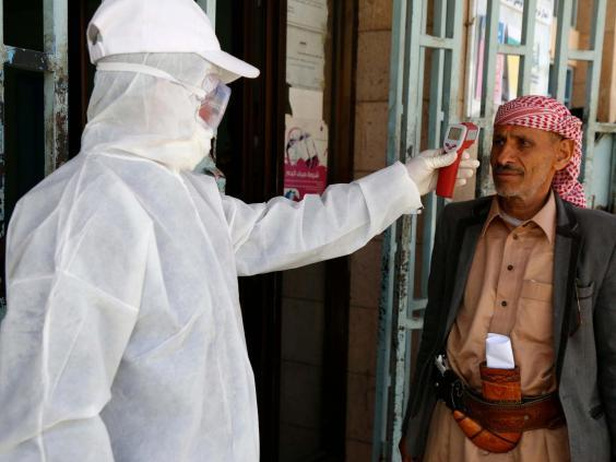 A medical worker measures the body temperature of a man at a state-run facility in Sana'a (Getty)