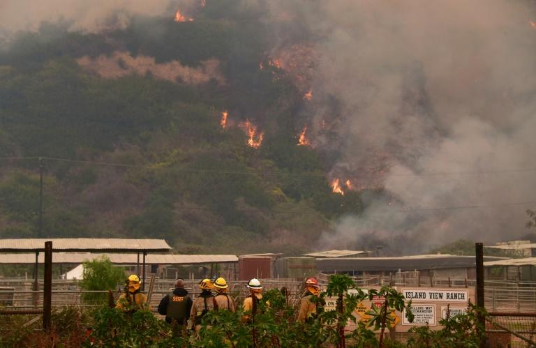 Firefighters and officials watch as fires burn near homes in La Conchita, California